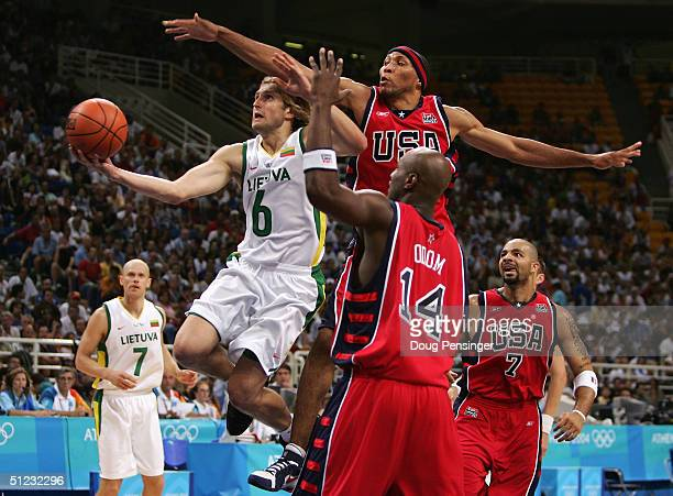 Arvydas Macijauskas of Lithuania shoots past the defense of Shawn Marion and Lamar Odom of the United States during the men's basketball bronze medal...