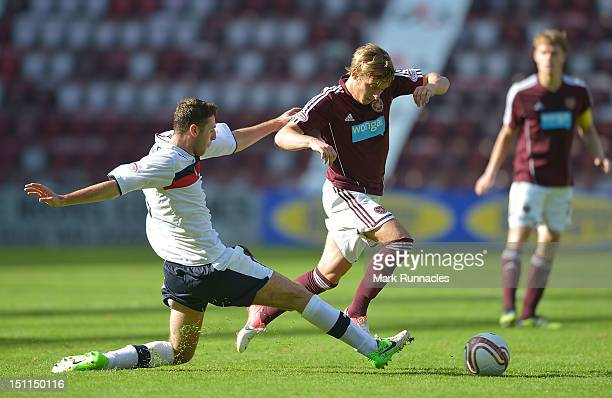 Arvydas Novikovas of Hearts is challenged by Lewis Toshney of Dundee during the Clydesdale Bank Scottish Premier League match between Hearts and...