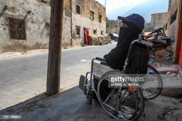 Arwa Naji, disabled after sustaining injuries during a Saudi-led coalition bombardment on her neighbourhood in 2015, sits on a wheelchair in front of...