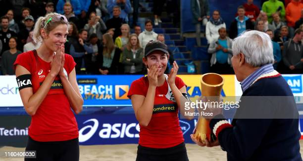Ary S. Graca, president of the International Beach Volleyball Federation hands over the trophy to Sarah Pavan and Melissa Humana Paredes of Canada...