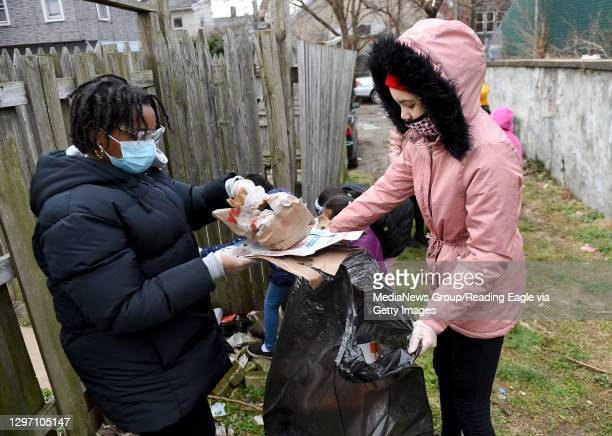 Arye'Anna Alvarado-Paz puts trash in the bag as Ariely Rodriguez holds the bag open for her. At the Olivet Boys and Girls Club Mulberry Street...