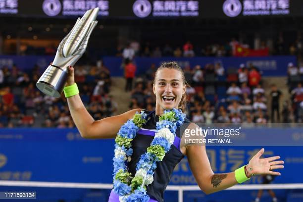 Aryna Sabalenka of Belarus holds the trophy after her victory in the women's singles final match against Alison Riske of the US at the Wuhan Open...