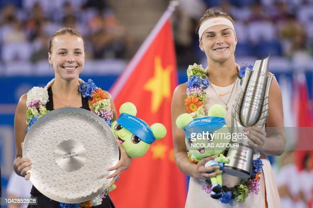Aryna Sabalenka of Belarus holds the trophy after she won the women's singles final match against Anett Kontaveit of Estonia at the WTA Wuhan Open...