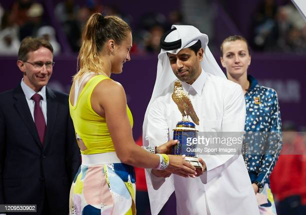 Aryna Sabalenka of Belarus is handed the championship trophy by Nasser AlKhelaifi president of Qatar Tennis Federation after winning the Women's...