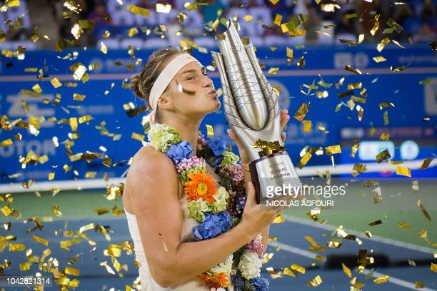 TOPSHOT Aryna Sabalenka of Belarus kisses the trophy after winning the women's singles final match against Anett Kontaveit of Estonia at the WTA...