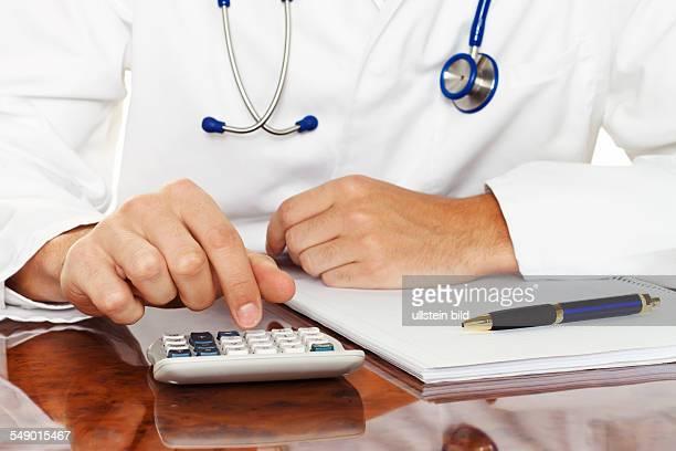 Arzt mit Taschenrechner Berechnung von Kosten und Einnahmen in Arztpraxis und Krankenhaus
