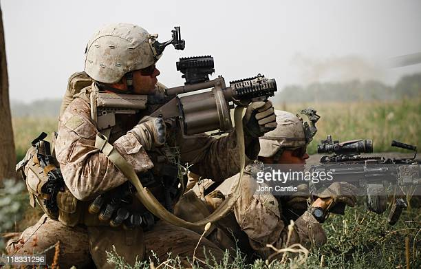 As 1st Platoon 3rd Battalion 4th Marines make a routine patrol in the upper Gereshk Valley Franklin Dickey fires grenades from the semiautomatic...