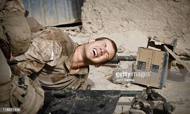 As 1st Platoon 3rd Battalion 4th Marines make a routine patrol in the upper Gereshk Valley Alfred Grossklaus shouts in pain after being shot in the...