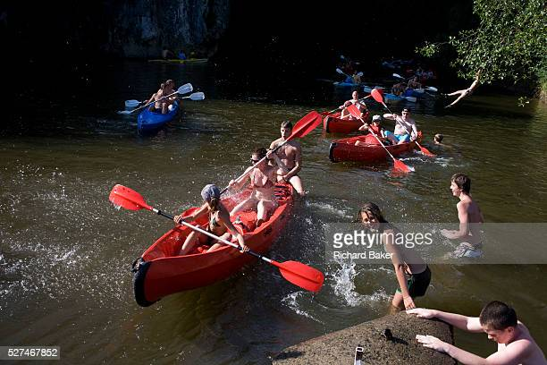 As a boy swings from a tree canoeists enjoy a day's paddling down the River Lesse Belgium's prime kayaking destination in the southern Ardennes...