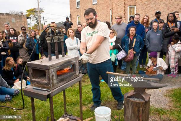 As a crowd watches American religious activist and blacksmith Michael Martin of the RAWTools organization uses a portable forge to make garden tools...