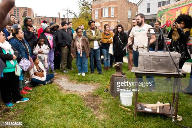 As a crowd watches American religious activist and blacksmith Michael Martin of the RAWTools organization demonstrates forming garden tool out of...