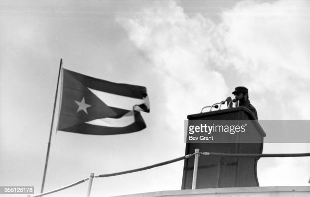 As a Cuban flag waves beside him military and political leader Prime Minister Fidel Castro speaks from a podium in la Plaza de la Revolucion during...
