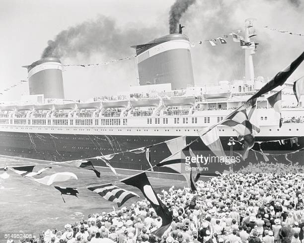 As a huge crowd on Pier 86 waves 'Bon Voyage' at her the superliner SS United States is pulled out of her berth in New York for her maiden voyage to...