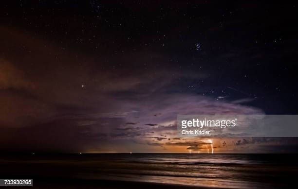As a lightning storm strikes the Atlantic Ocean off Cocoa Beach, Florida, a meteor streaks over the storm