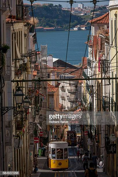 As a local leans out from a window above and others walk uphill one of the two cars of the funicular railway climbs the steep gradient of on Rua de...