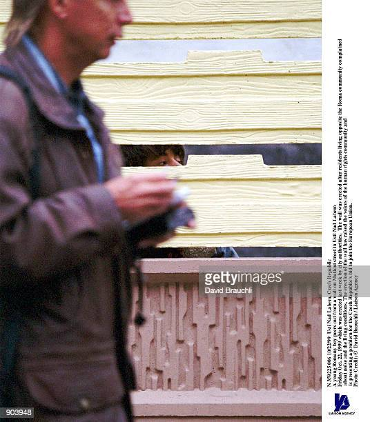 As a man walks on Maticni street in Usti Nad Labem Friday Oct 22 1999 as a young Romany boy peaks through a wall erected last week by city...