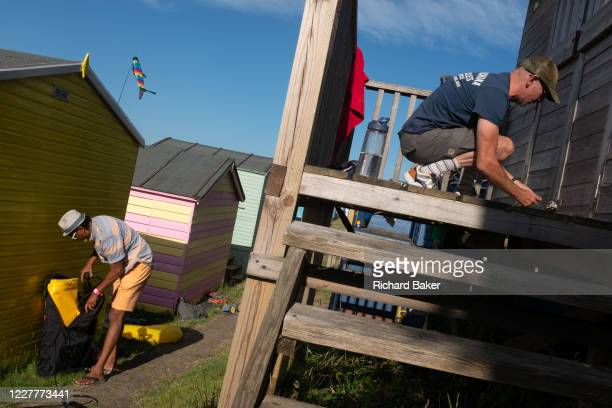 As a neighbour packs away beach equipment another ensures that all doors and locks are secured on a beach hut on the seaside promenade on 18th July...