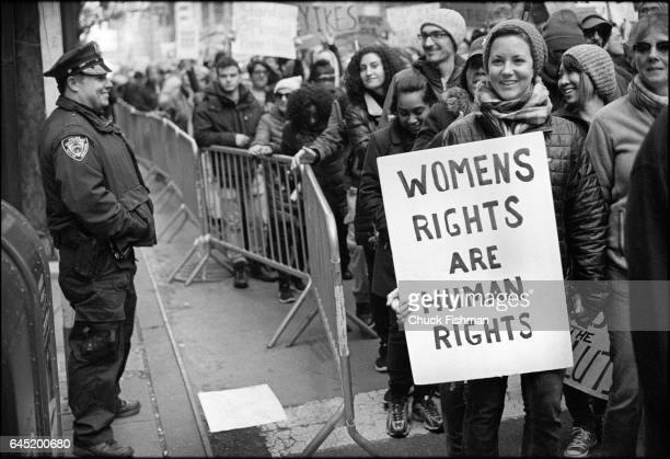 As a policeman watches demonstrators participate in the Women's March on New York New York New York January 21 2017 One woman holds a sign that reads...