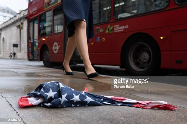 As a red London bus passes-by, a pair of legs walk past an American Stars and Stripes flag bandana lying on the wet pavement in the City of London,...