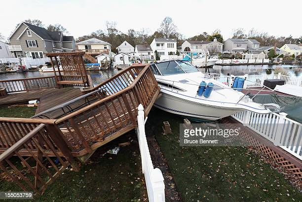 As a result of Hurricane Sandy a boat and damaged deck come to rest in the backyard of a home on Narraganset Avenue on October 31 2012 in Seaford New...
