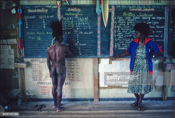 As a teacher watches a student works out math problems on a chalkboard during weekly traditional dress day in a classroom Tabubil Papua New Guinea...