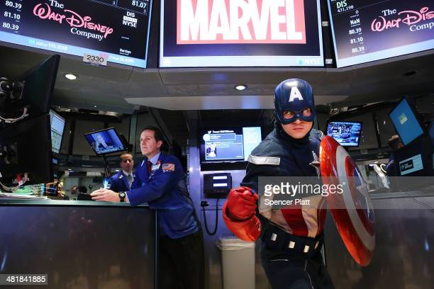As a trader works Captain America poses for photographers on the floor of the New York Stock Exchange after ringing the Opening Bell on April 1 2014...