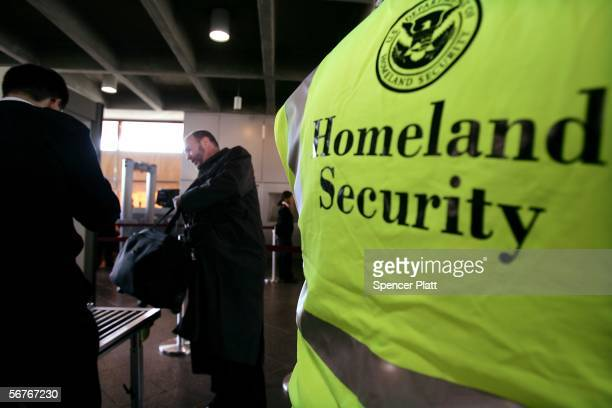 As a US Department of Homeland Security official stands by commuters place bags onto a weapondetection machine at Exchange Place station on the first...