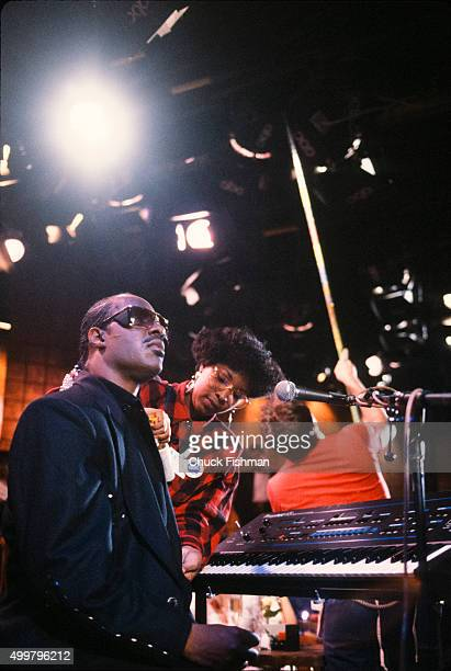 As a wardrobe specialist adjusts his jacket American Jazz and Pop musician Stevie Wonder sits a piano on the set of the television soap opera 'All My...