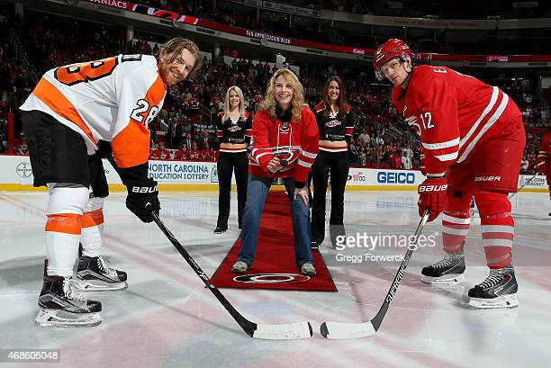 As a winner of the 30 Prizes in 30 Days promotion Carolina Hurricanes season ticket holder Joanna Moore participates in a ceremonial puck drop with...