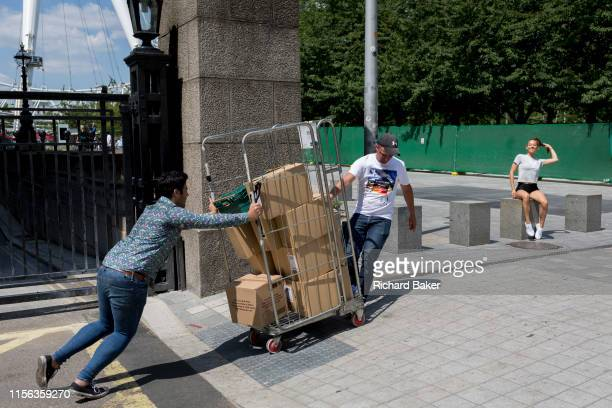 As a young woman poses for photos on the Southbank, deliverymen push a cage of unstable, then toppling boxes, on 16th July 2019, in London, England. .
