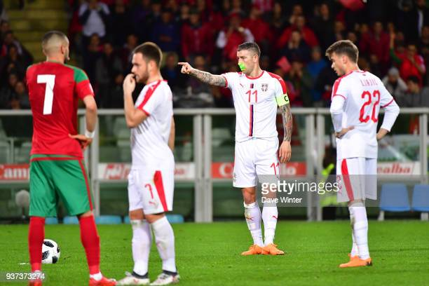 As Aleksandar Kolarov of Serbia waits to take a free kick a supporter shines a laser in his face during the international friendly match between...