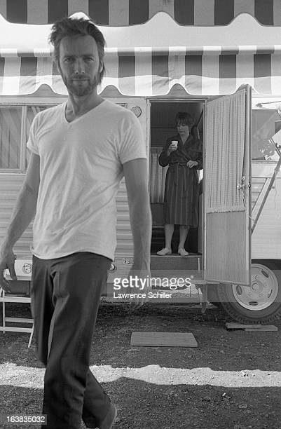 As American actress Shirley MacLaine stands in an open trailer doorway American actor Clint Eastwood walks past during a break in filming their movie...
