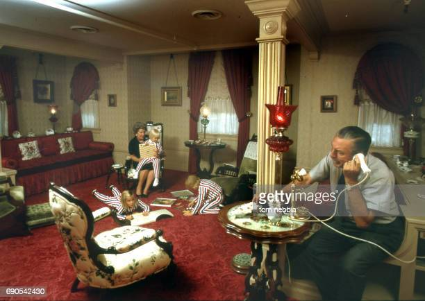 As American film producer and studio executive Walt Disney talks on the telephone his wife Lillian Disney plays with three of their grandchildren...