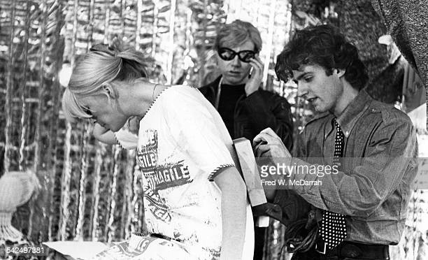 As American pop artist Andy Warhol watches poet Gerard Malanga stencils on the back of the dress worn by Germanborn model and singer Nico in front of...