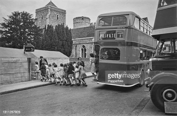 As an air raid siren sounds, a group of school children run from a double decker bus to the safety of a bomb shelter next to Holy Cross Church near...