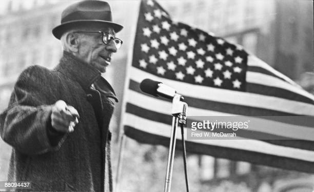 As an American flag waves behins him Dutchborn American social and political activist AJ Muste speaks from a microphone at an AntiDraft demonstration...