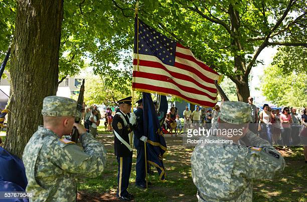 As an honor guard of US military veterans stand with flags in Vergennes City Park soldiers from the Vermont National Guard fire a round in salute...