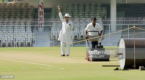 As an Indian groundsman continues to cut the grass surface of the pitch, Kishor Pradhan , curator and chairman of ground committee indicates this...