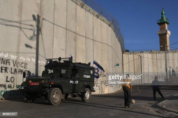 As an Israeli police patrol passes by Palestinian boys play under Israel's separation barrier May 4 2008 where the controversial 30foothigh wall cuts...