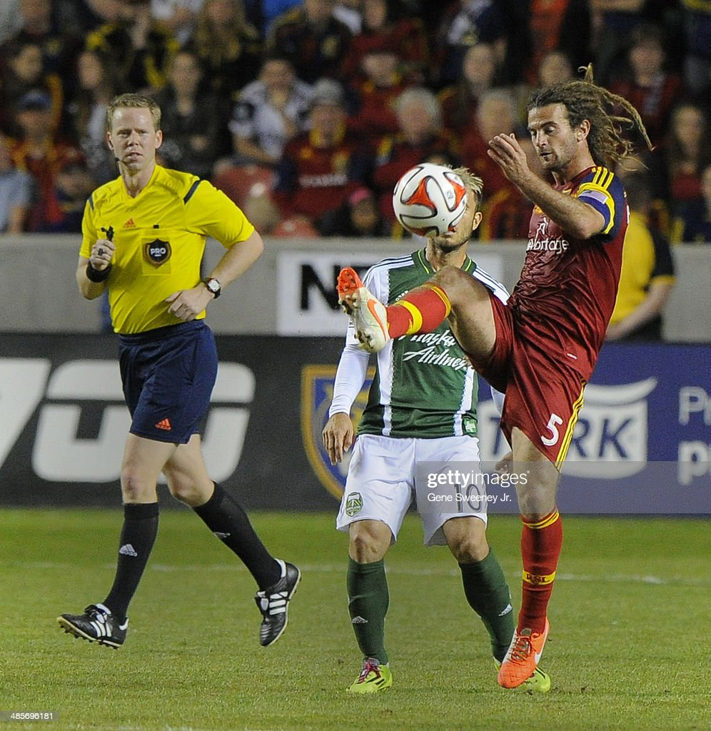 As an official looks on, Kyle Beckerman #5 of Real Salt Lake kicks the ball away from Gaston Fernandez #10 of the Portland Timbers during the second half at Rio Tinto Stadium April 19, 2014 in Sandy, Utah. Real Salt Lake won 1-0.