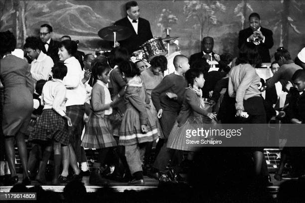 As an unidentified band plays behind them, a group of children and adults dance at the Apollo Theater, New York, New York, 1961.