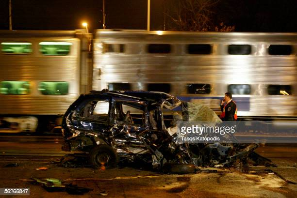 As another Metra train passes a worker stands amidst the wreckage after a Metra train crashed into about five vehicles which hit another ten cars at...
