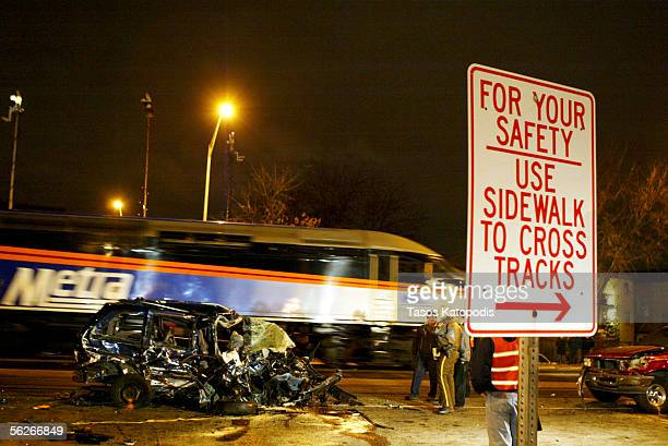 As another Metra train passes workers stand amidst stand amidst the wreckage after a Metra train crashed into about five vehicles which hit another...