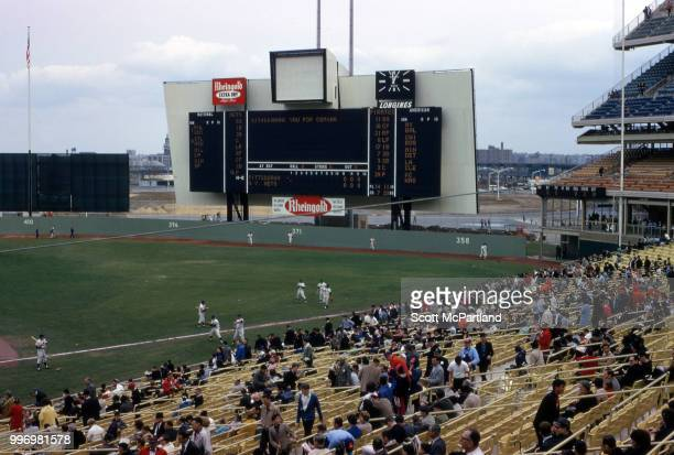 As baseball players warm up on the grass spectators in the stands attend opening day at Shea Stadium New York New York April 17 1964 The day marked...