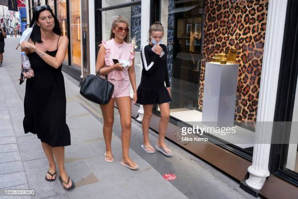 As Britain enters a period of deep recession, as the economic downturn caused by the Covid-19 pandemic cuts, shoppers wearing face masks continue to...