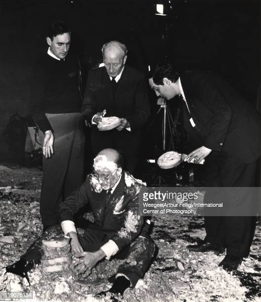 As British film director Stanley Kubrick and two unidentified crewmen stand behind him, British actor Peter Sellers sits on the cream pie-covered...