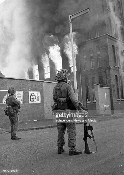 As buildings burn British Army troops patrol the streets after being deployed to end the Battle of the Bogside Derry Northern Ireland August 15 1969...