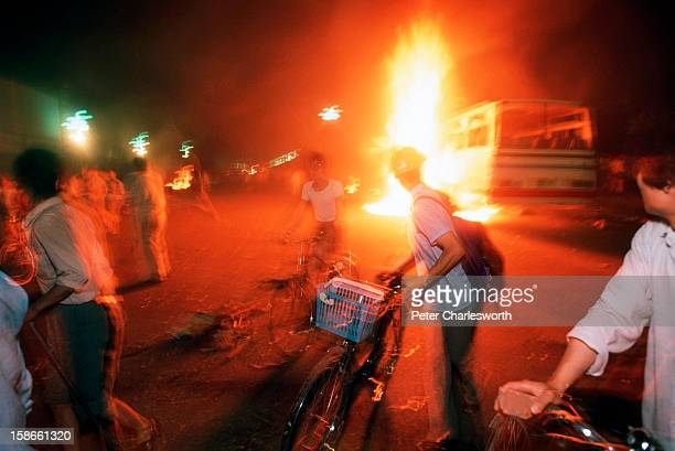 As buses and vehicles burn, pro-democracy demonstrators retreat down Changan Avenue as soldiers march and shoot their way towards Tiananmen Square on...