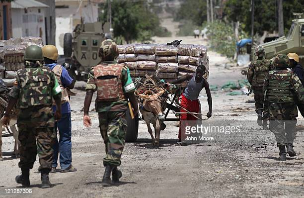As business slowly begins anew a laborer moves goods past Ugandan African Union soldiers in the Bakara market on August 17 2011 in Mogadishu Somalia...