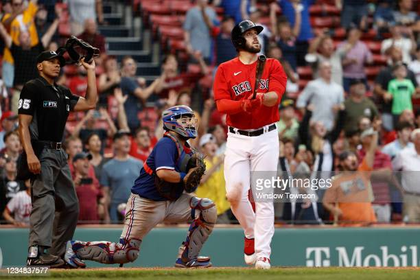 As catcher Jose Trevino of the Texas Rangers and umpire Jeremie Rehak look on, Travis Shaw of the Boston Red Sox watches his game winning grand slam...